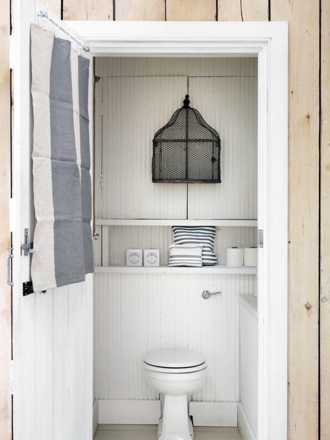 Toilettes, rembourrées à l'intérieur avec des clins légers et des étagères déguisées en dessous