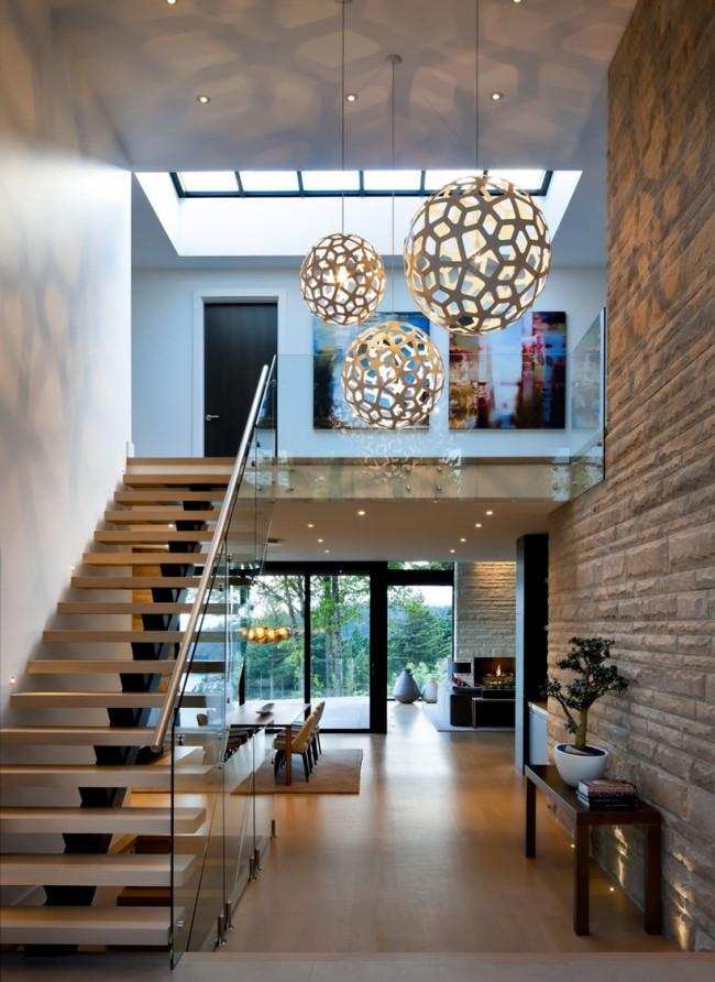 Combinaison avec le métal et le verre dans un intérieur moderne.  L'éclairage ponctuel de la pierre texturée par le bas semble également très intéressant.
