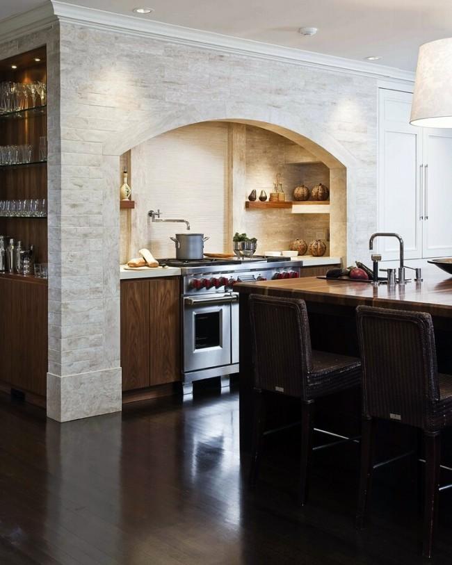Voûte luxueuse, bordée de pierre et cachant la hotte, au-dessus du plan de travail de la cuisine