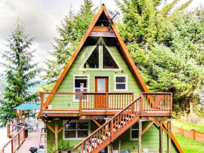 Une maison soignée en forme de hutte à deux étages avec un escalier extérieur
