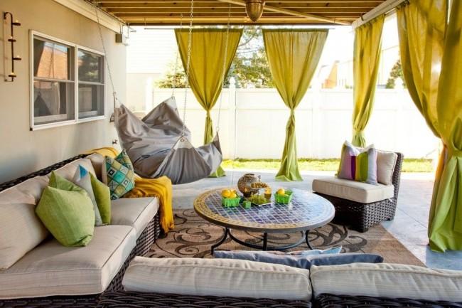 La chaise suspendue en forme d'oreiller a l'air confortable sur la terrasse d'été