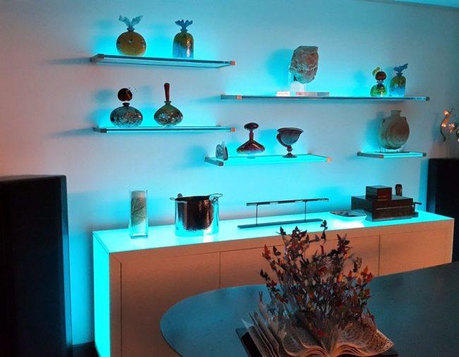 Le rétroéclairage bleu des étagères du salon peut modifier favorablement le contour des objets de décoration