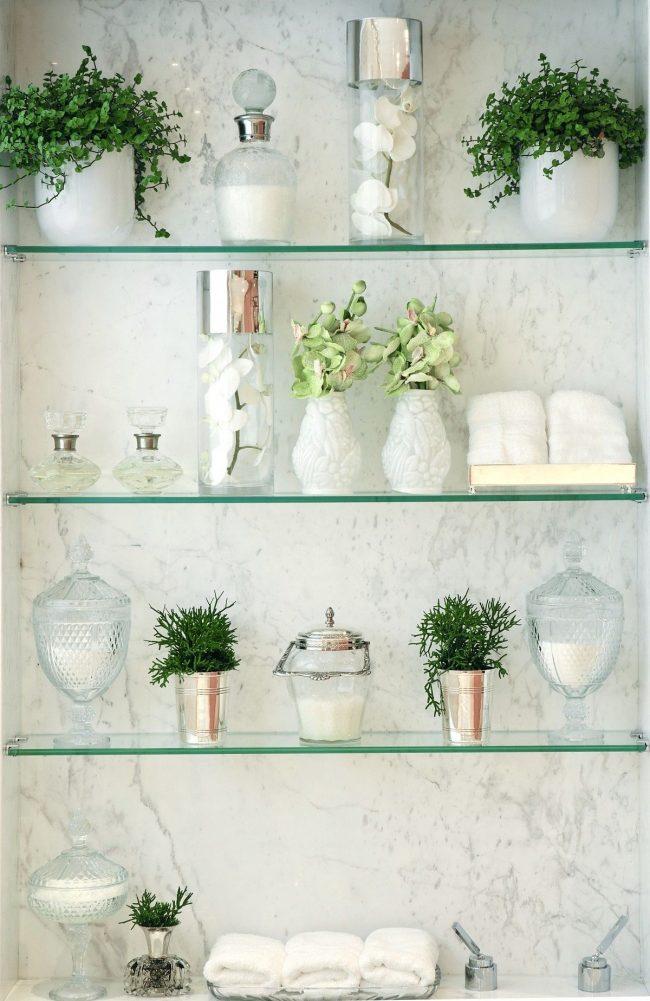 Un exemple de décoration d'un mur de salle de bain à l'aide d'étagères en verre mince, de plantes et d'articles de toilette