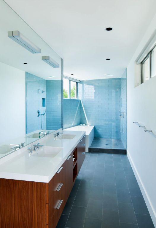 Les carreaux de verre bleu dans une salle de bain étroite ajoutent un accent de couleur vibrante