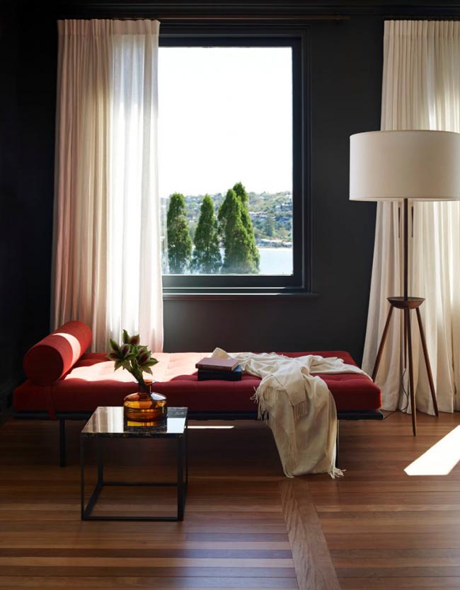 Le canapé rouge a fière allure avec des murs sombres