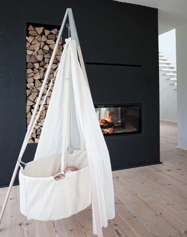 Intérieur scandinave avec tas de bois, cheminée et berceau pour bébé