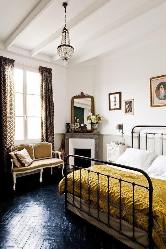 Le parquet de couleur résine noire combiné à un lit en fer forgé rend la pièce intéressante