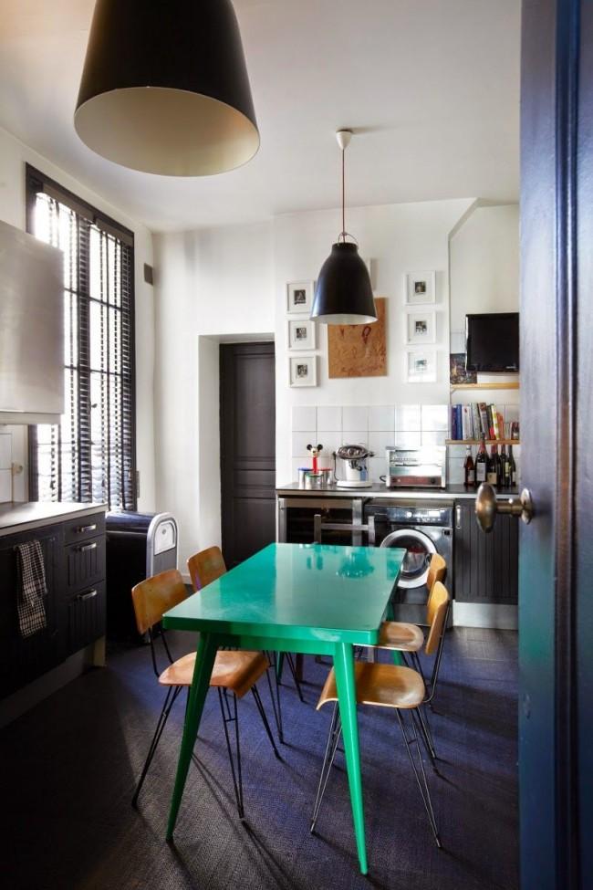 Petite table turquoise sur sol sombre au centre de la cuisine