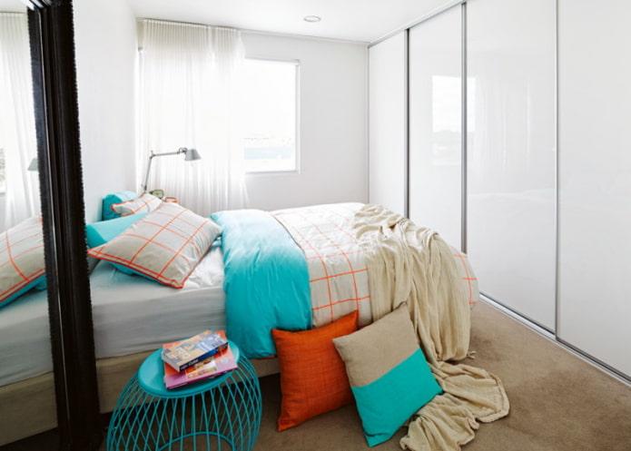 Lit en face du meuble avec portes brillantes