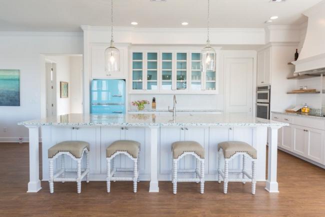 Réfrigérateur signature Smeg de couleur bleu vif dans une cuisine spacieuse aux couleurs claires.  Plus loin dans l'article, vous pouvez également voir une variété de réfrigérateurs de cette marque.