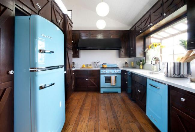 Une combinaison audacieuse d'un ensemble de cuisine sombre avec des appareils électroménagers bleu vif dans une petite cuisine