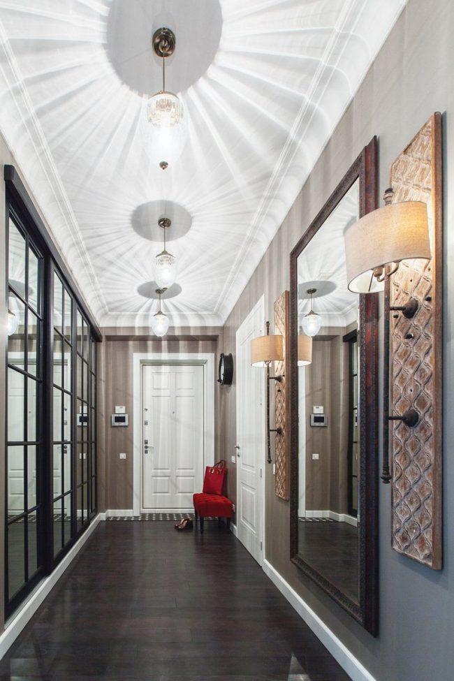 Belle salle avec un mur en miroir et un grand miroir en face dans un cadre en bois