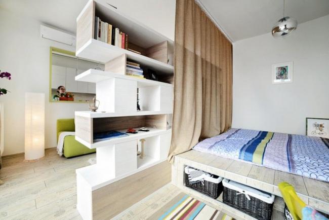 Studio moderne dans lequel les étagères font office de cloison entre les deux zones principales du logement