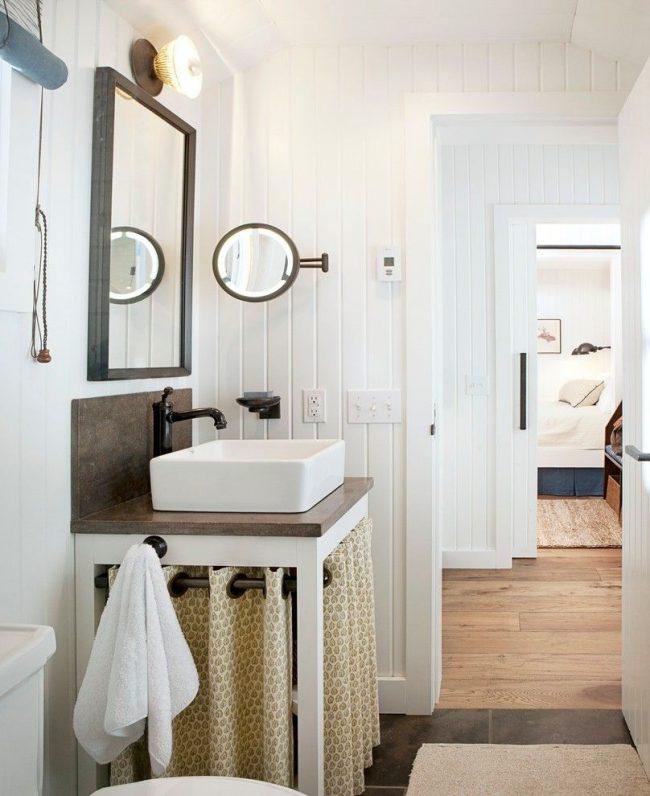 Mini-maison exquise avec toilettes et douche.  Le lavabo est en porcelaine et les accessoires de salle de bain sont en laiton.  Il y a aussi beaucoup de bois dans la décoration.