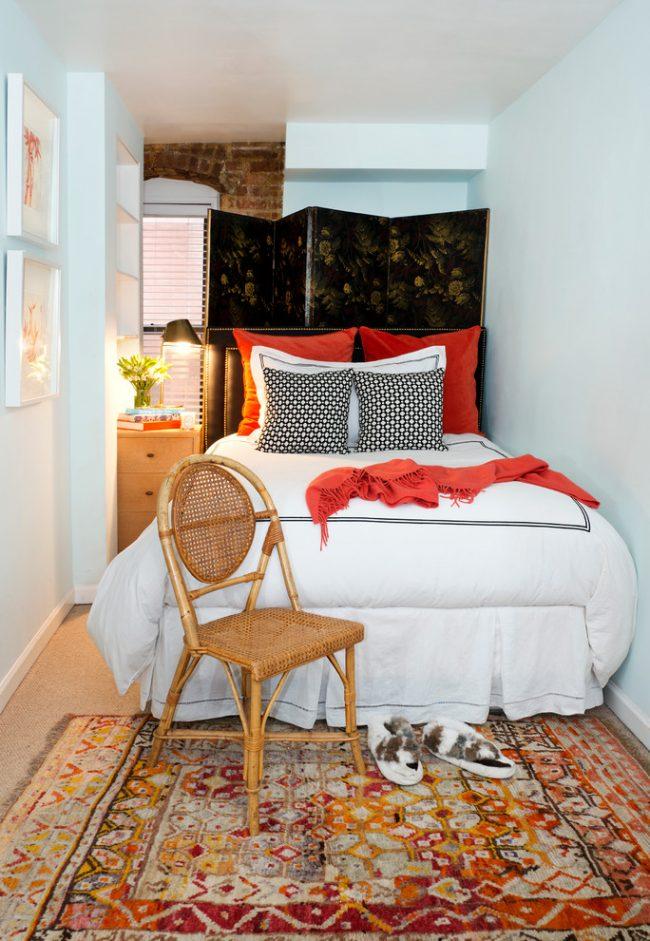 Chambre étroite avec des murs blancs et des textiles confortables aux couleurs chaudes