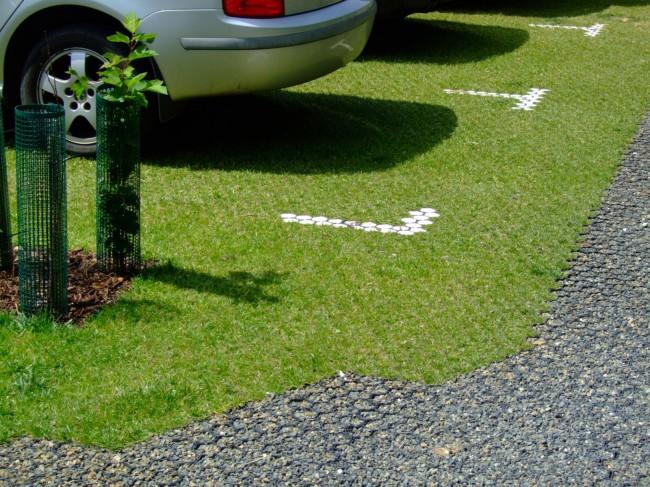 Petit parking sur une aire bordée d'une pelouse en treillis