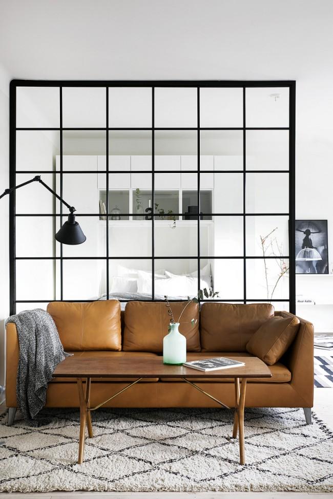 Canapé luxueux à la frontière de la zone nuit et du salon dans un appartement d'une pièce