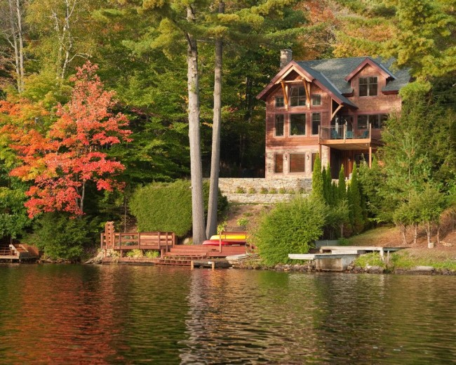 Magnifique vue sur une maison à ossature sur fond de forêt et d'un lac