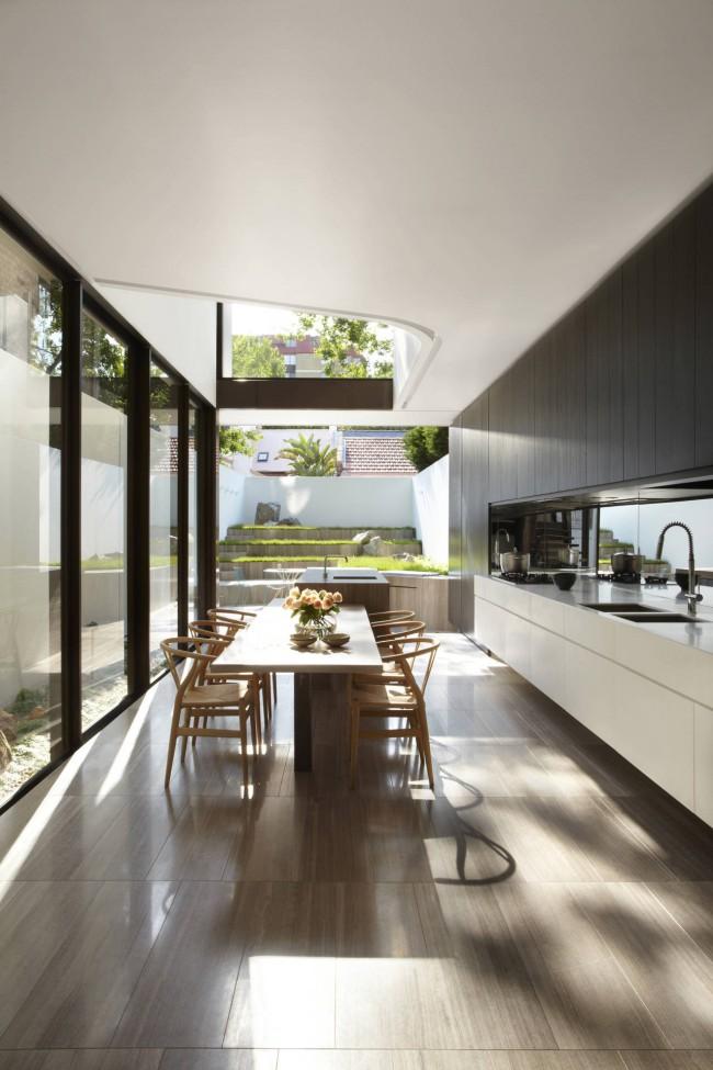 Cuisine-studio très spacieuse dans une maison privée avec du wengé foncé dans la conception de la zone de travail et de la lumière dans la salle à manger