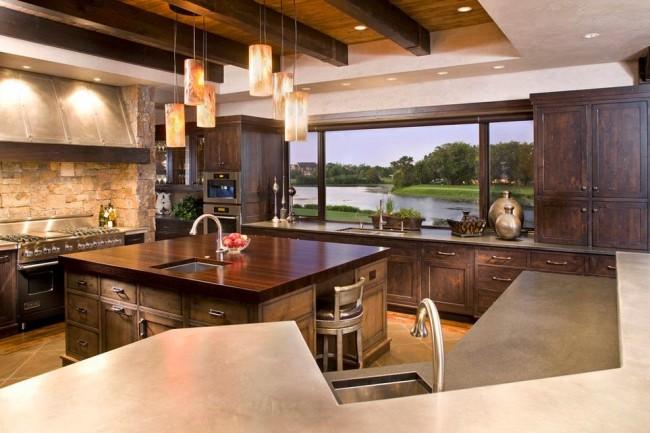 Cuisine studio très luxueuse aux couleurs chaudes avec une utilisation maximale du wengé dans la décoration du bloc cuisine, ainsi que le plan de travail d'une des surfaces de travail