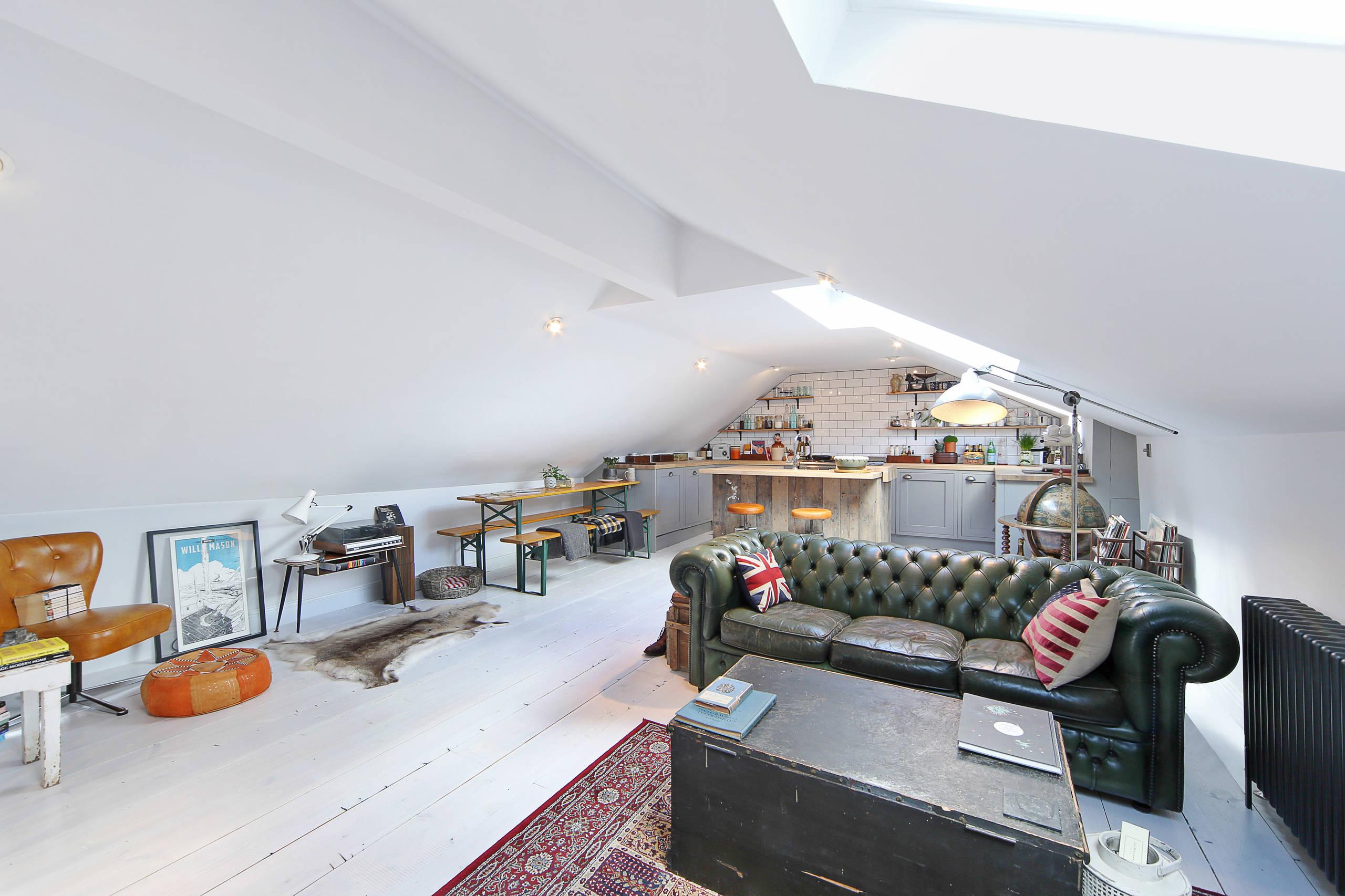 Appartement loft avec un plafond géométriquement complexe, un mobilier simple et fonctionnel avec un effet vieillissant, un canapé en cuir au centre de la pièce et différentes conceptions d'éclairage