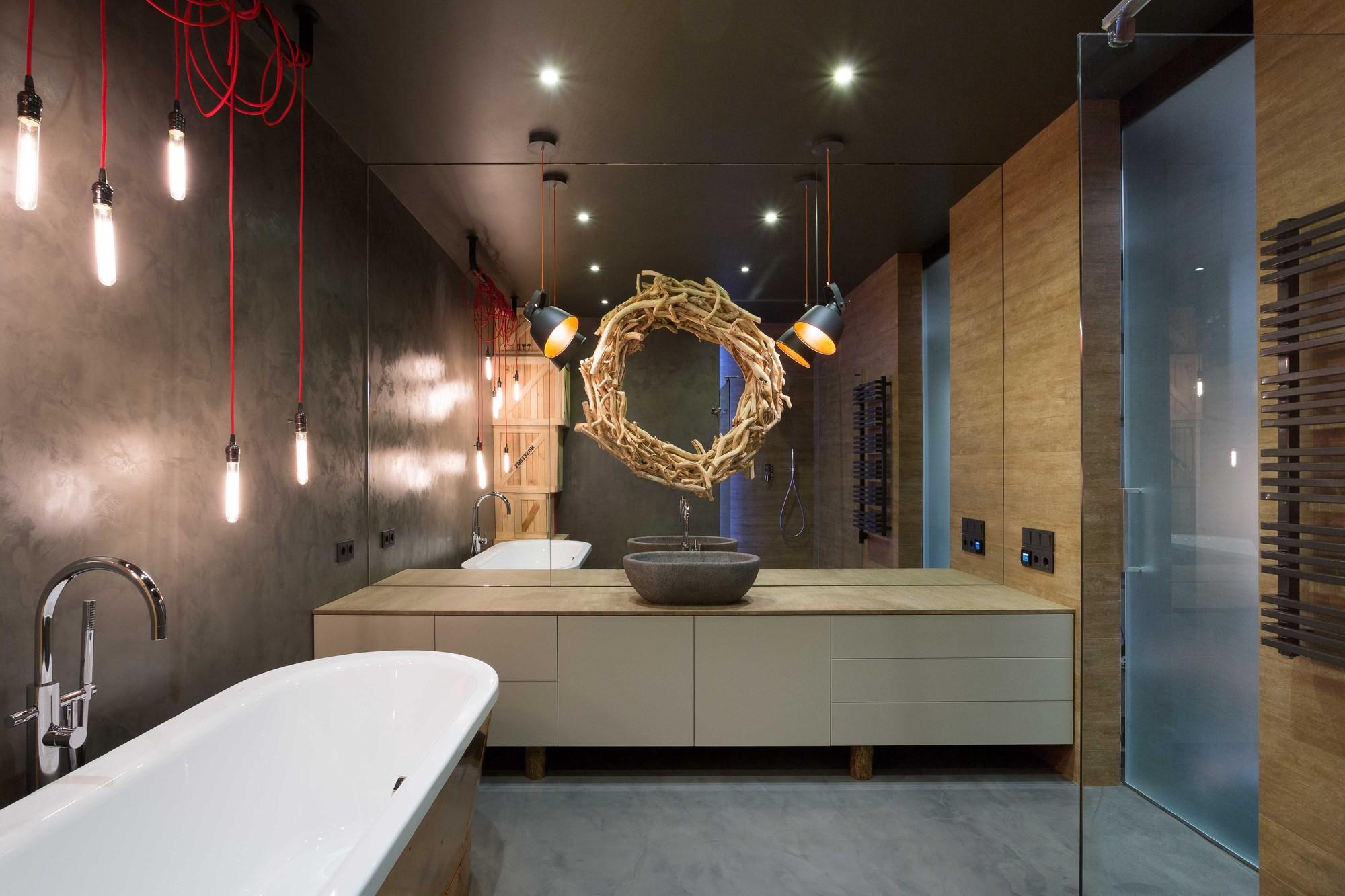 Couleurs sombres, formes simples de plomberie, armoires de salle de bain à panneau plat, système d'éclairage original définit le style général du loft