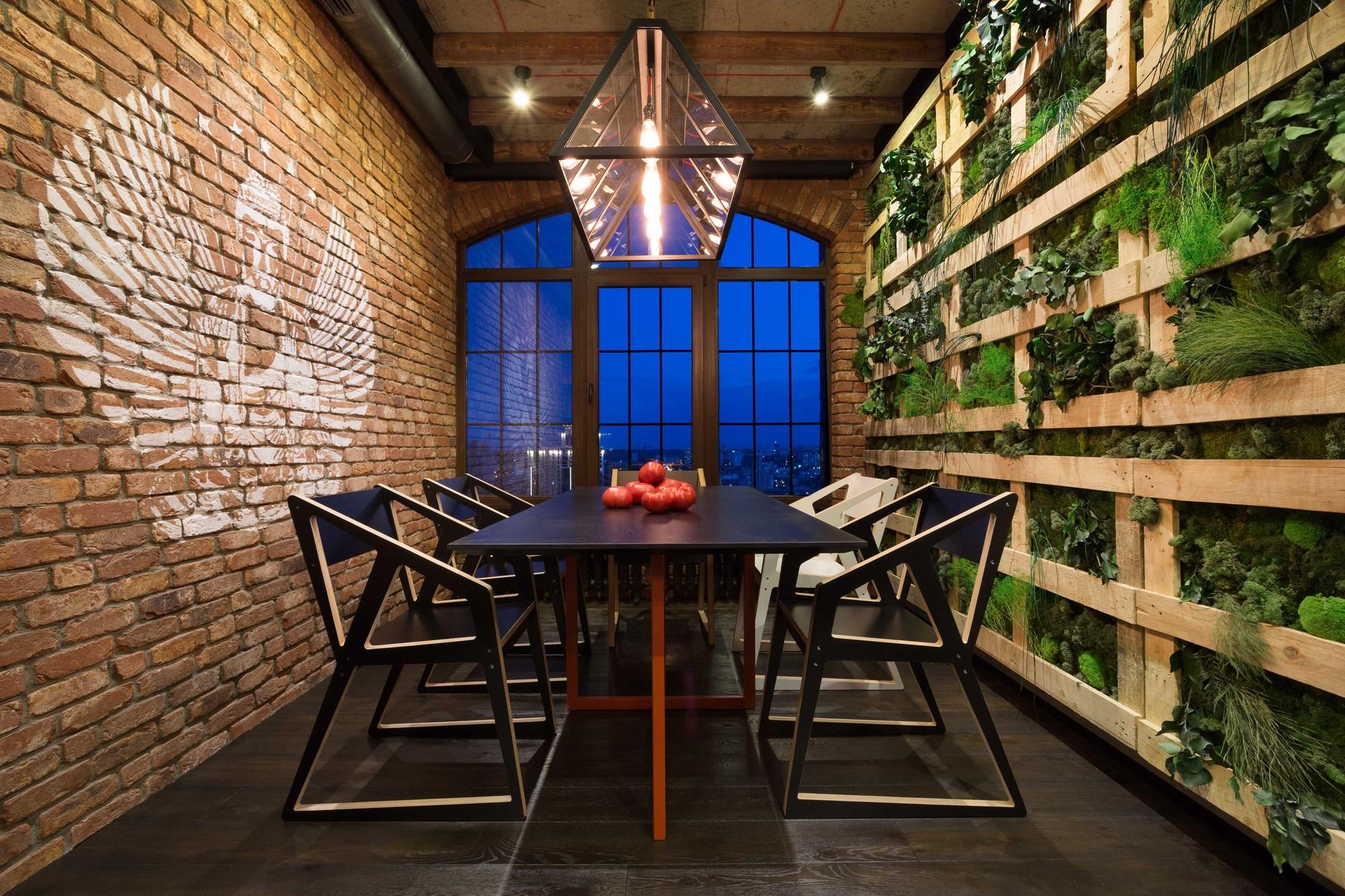 Salle à manger de style loft laconique du groupe de designers MARTIN architects : mur de briques avec végétation opposée, sol noir, mobilier minimaliste, structure lumineuse géométrique