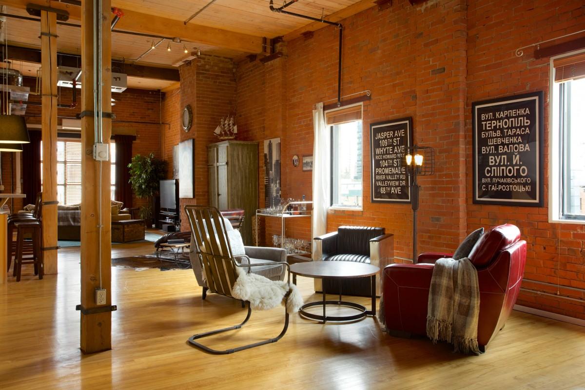 Un appartement de style loft moderne avec un éclairage mixte qui dicte les zones de la pièce sans cloisons.  Une table basse ronde, quatre fauteuils assortis et un lampadaire en métal brut forment un coin lecture