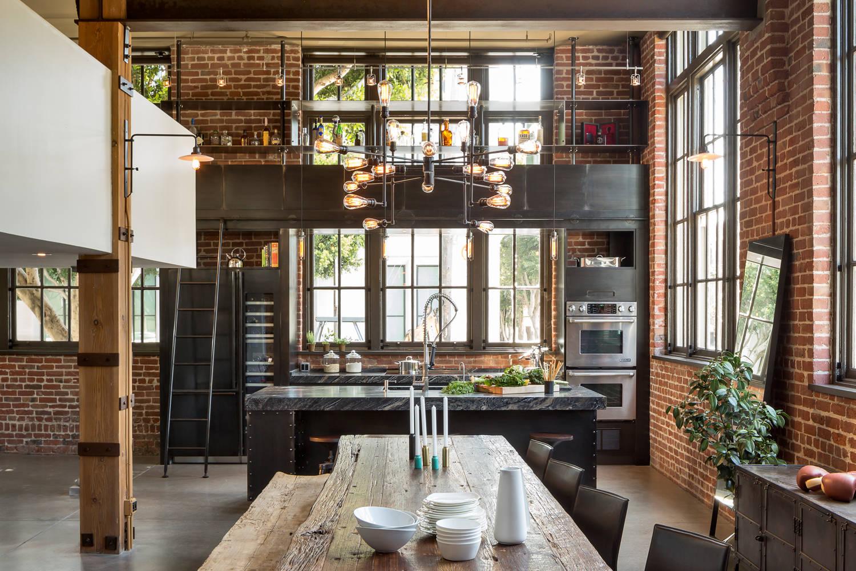 Une cuisine caractéristique de style loft avec une abondance de brique, de bois et de métal dans la décoration.  Les lampes Edison dans des conceptions de rails combinées et des appliques murales soulignent le thème général