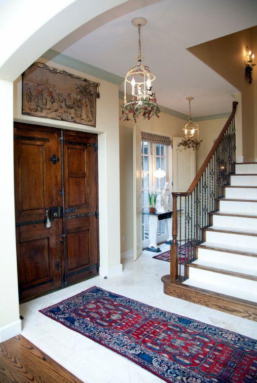 Le hall lumineux d'une maison de campagne de style provençal est décoré de portes en bois sombre