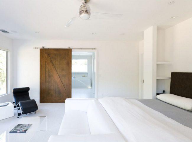 Portes en bois brut foncé dans un intérieur blanc minimaliste