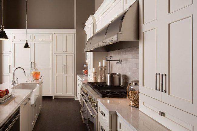 Exigences de base concentrées pour un intérieur classique, illustrées par une cuisine blanche avec des plans de travail en quartzite et des finitions murales de couleur latte