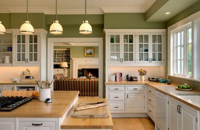La couleur verte discrète du papier peint, l'ensemble de cuisine blanc, le parquet et les plans de travail sont le design intérieur d'une cuisine classique.  L'utilisation de formes et de combinaisons strictes est la règle de style