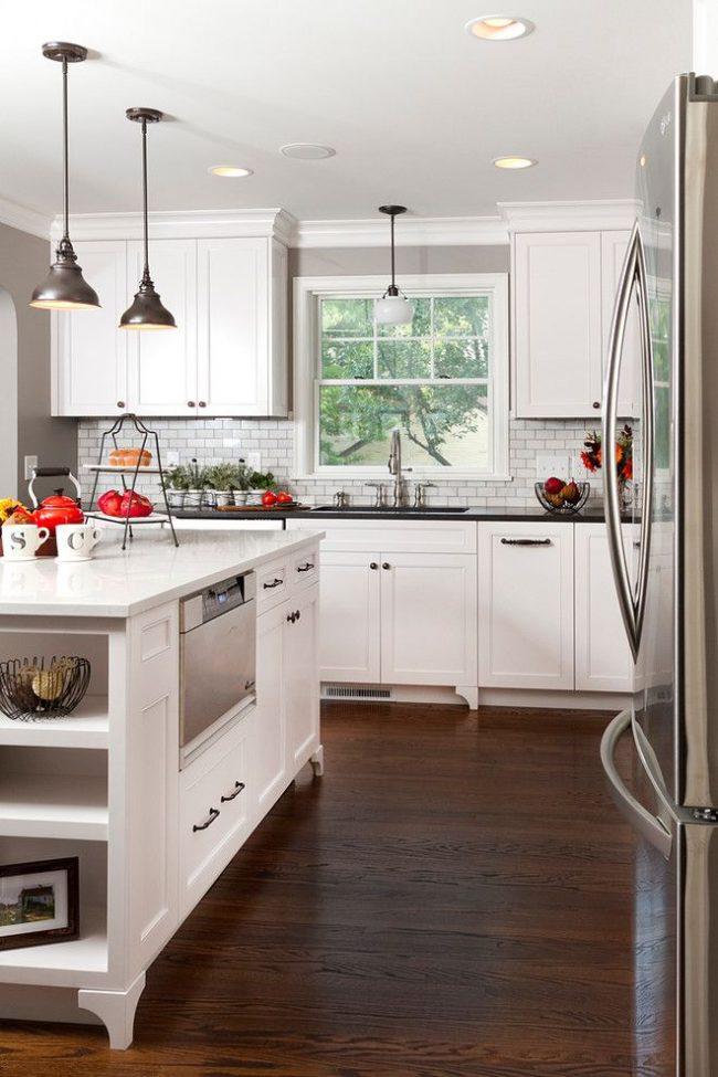 La façade blanche des armoires de cuisine inférieures et le comptoir noir sont la décoration de l'espace de travail principal.  L'îlot de cuisine est entièrement fini en matériaux blancs et est multifonctionnel