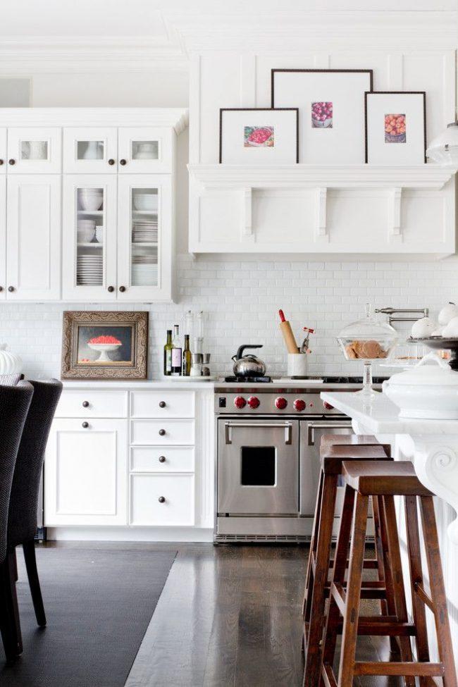 Cuisine blanche classique avec des plats en porcelaine cachés derrière les façades de la cuisine, une table à manger avec des moulures en stuc en plâtre, une peinture de l'auteur et d'autres éléments intérieurs