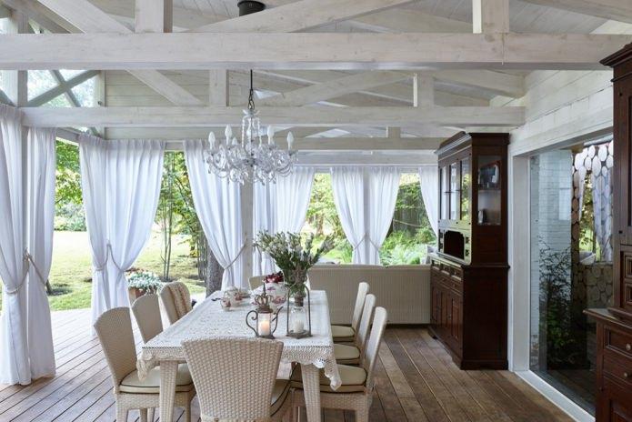 rideaux blancs avec embrasses sur la véranda d'une maison de campagne