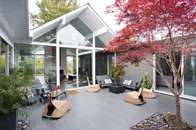 Le projet original d'une maison moderne de plain-pied avec une terrasse dans la cour à deux zones.  Le premier est un espace vert avec des plantes, le second est un espace détente avec fauteuils et canapés