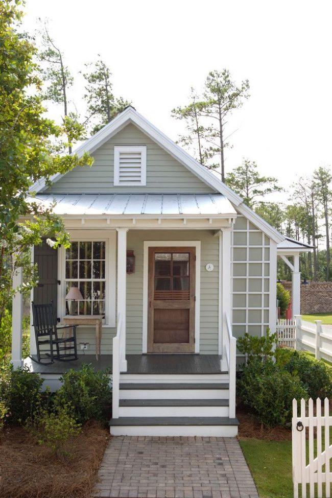 Maison compacte de plain-pied avec une petite terrasse combinée à un porche, un territoire attenant verdoyant et un garage avec un drive-in séparé