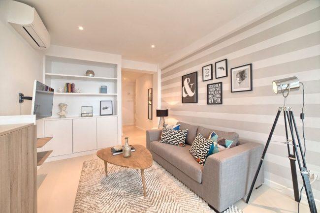 Les rayures horizontales sur le papier peint de l'un des murs du salon augmentent visuellement l'espace