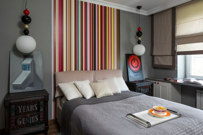 Les rayures verticales du papier peint à la tête du lit contribuent à augmenter la hauteur du plafond
