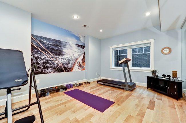 Salle de gym à domicile avec papier peint photo sur l'un des murs