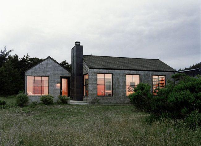 Maison en briques grises à un étage avec de grandes fenêtres