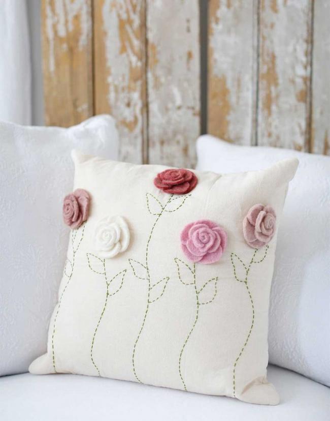 L'oreiller blanc peut être décoré de petites fleurs en textile doux