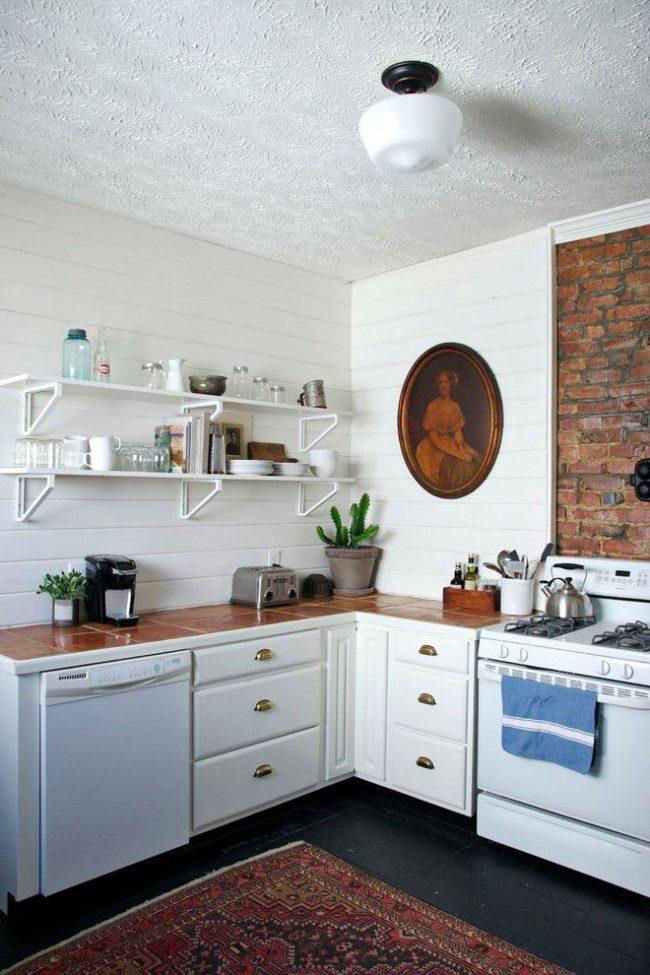 Un portrait antique dans un cadre ovale a fière allure dans cette cuisine