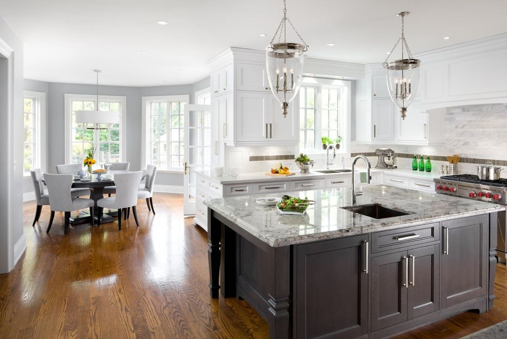 Une baie vitrée à côté de la cuisine crée délicatement une salle à manger séparée et cosy, la séparant du salon