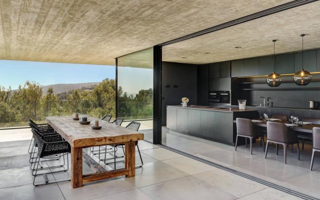 La cuisine avec des fenêtres panoramiques et des meubles sombres est très élégante