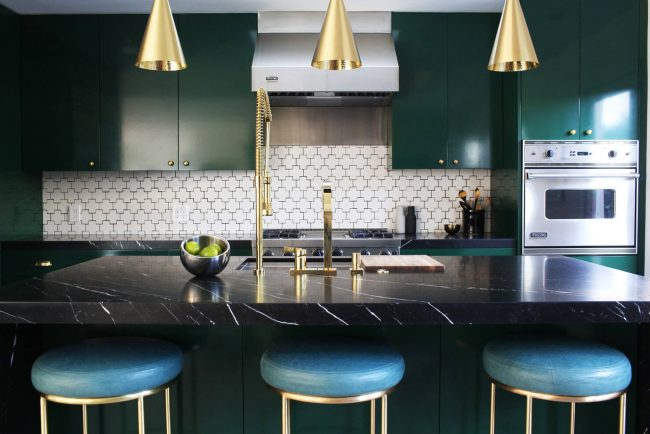 Façades brillantes, plans de travail en marbre noir et spots originaux dans une cuisine Art Nouveau émeraude