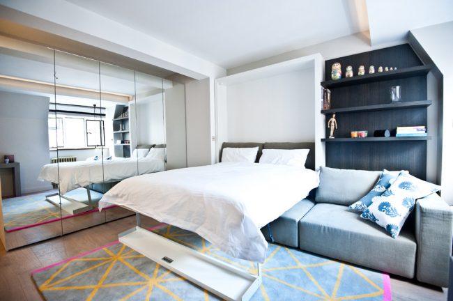 Même le design du lit transformable chambre à coucher, qui est caché dans le mur, économisera parfaitement de l'espace dans une petite chambre-salon d'une superficie de 18 m².  m peut être très confortable et beau