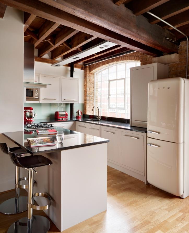 Dans le style loft, une cuisine blanche avec un réfrigérateur vintage a l'air très organique
