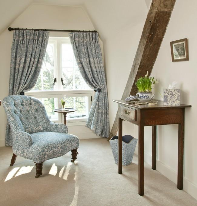 Fauteuil et rideaux dans le même motif floral dans un intérieur de style campagnard